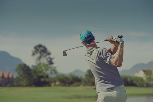 A man swinging on a golf court