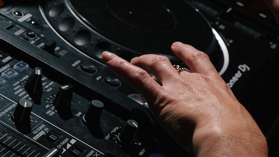 A DJ using a Pioneer CDJ 2000 NXS2 set up for beginners in a Pirate Studios DJ room
