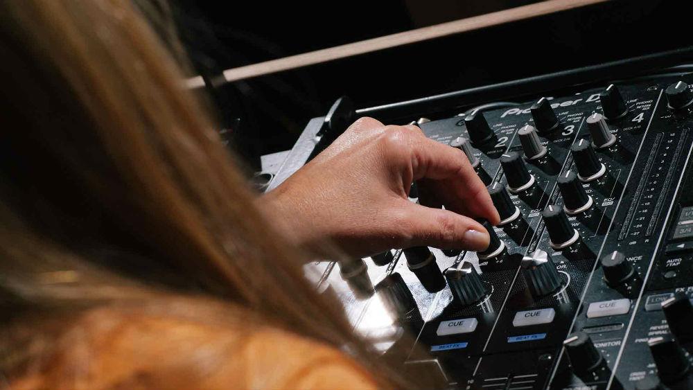 A DJ using a Pioneer DJM 900 NXS2 DJ set up for beginners in a Pirate Studios DJ room