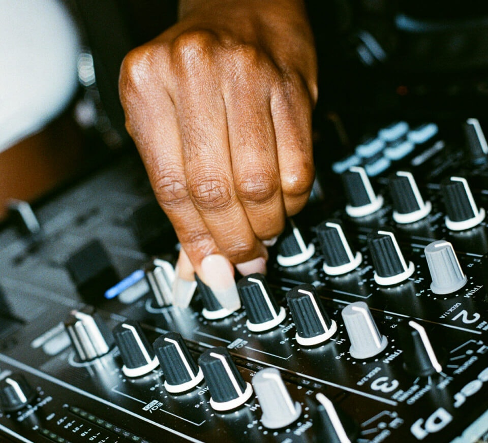 Close up shot of a DJ using a Pioneer DJM-900NXS2 inside a Pirate Studios DJ studio