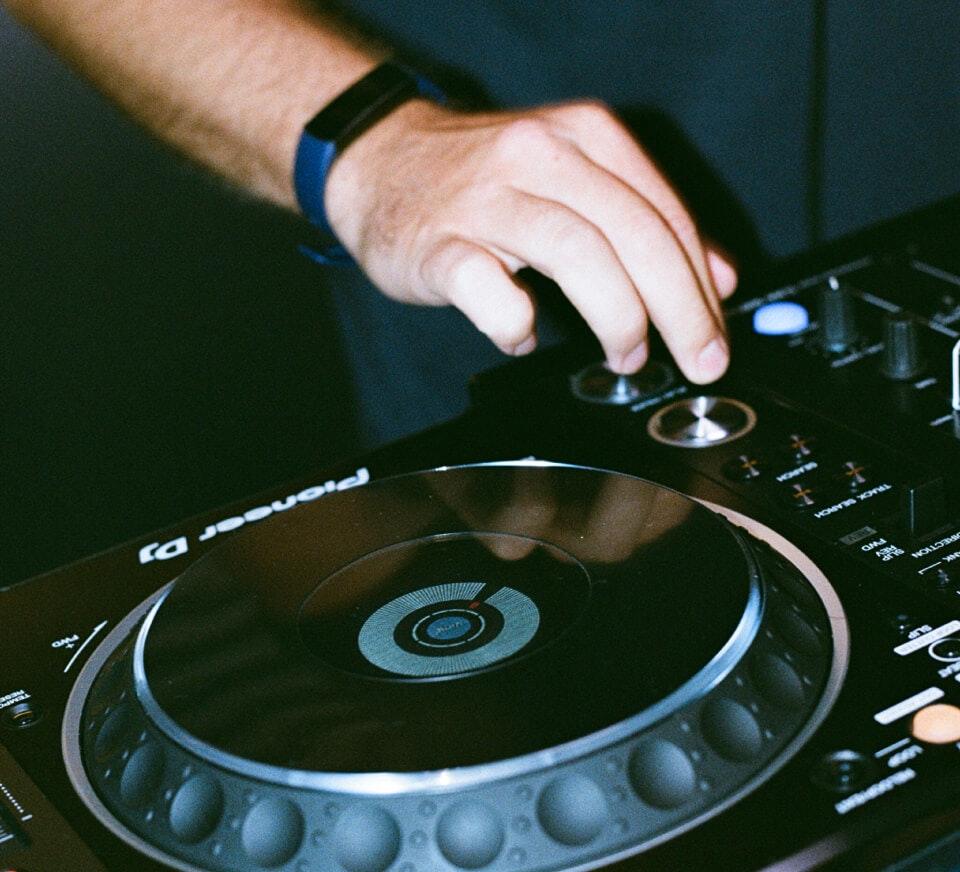 Close up shot of a DJ using a Pioneer DJM-900NXS2 and CDJ-2000NXS2 inside a Pirate Studios DJ studio