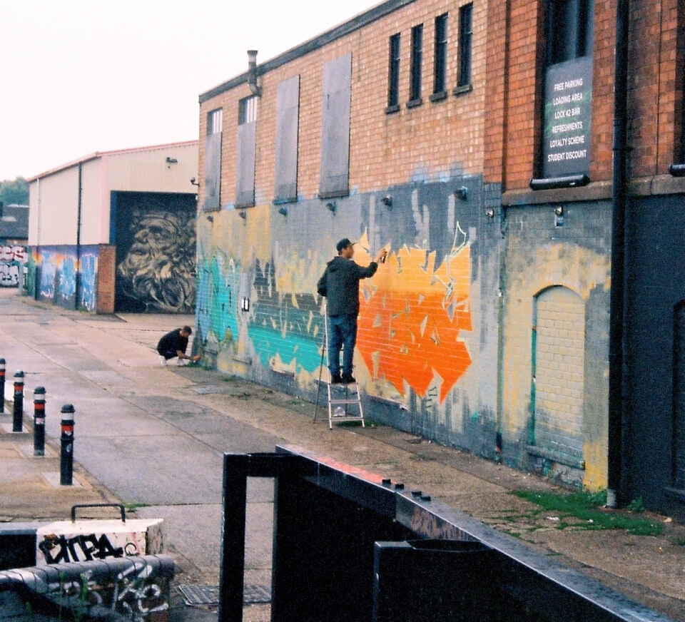 Graffiti artist painting a residential wall close to Pirate Studios Leicester