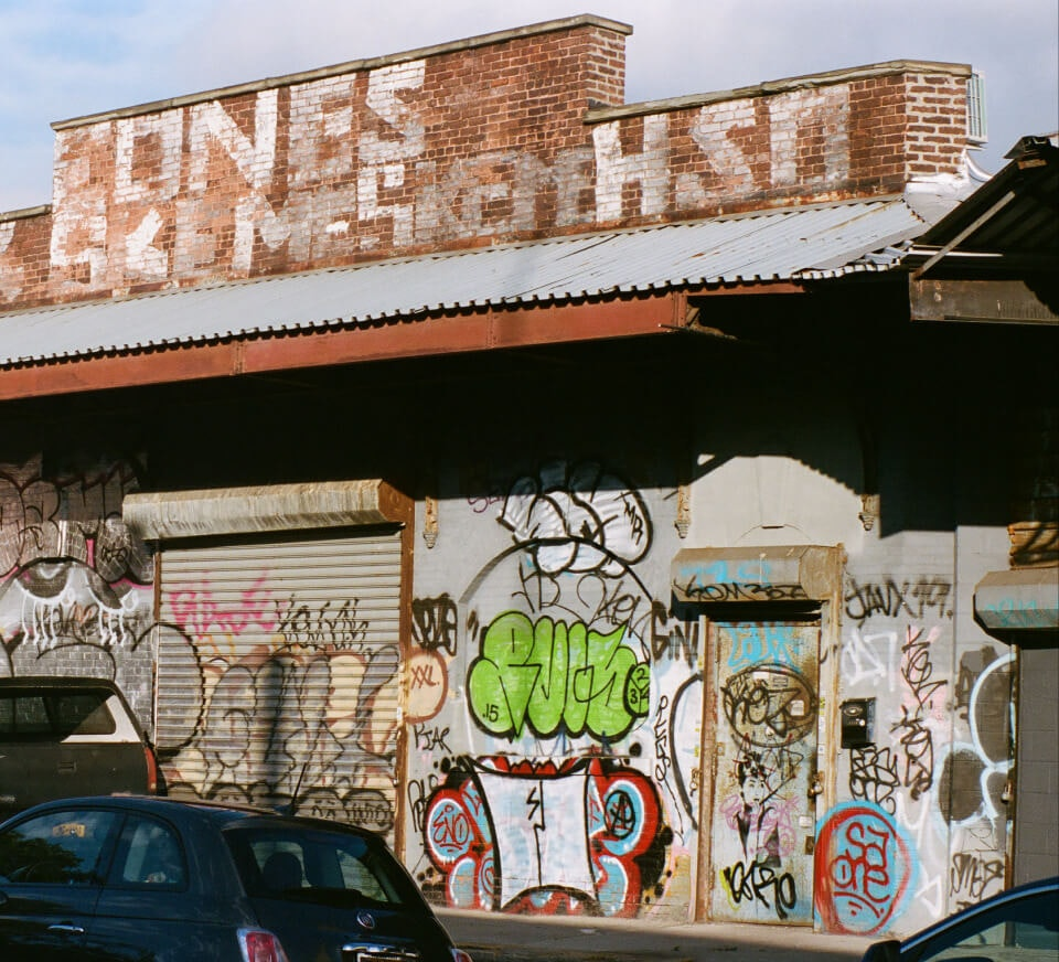 An exterior wall with graffiti and a car in the foreground on a Chicago street. Creative stuios for musicians, podcasters and dancers coming soon.