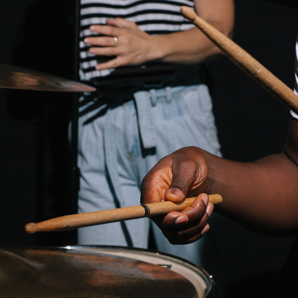 This image may contain: musician, person, musical instrument, human, drummer, percussion, drum, finger