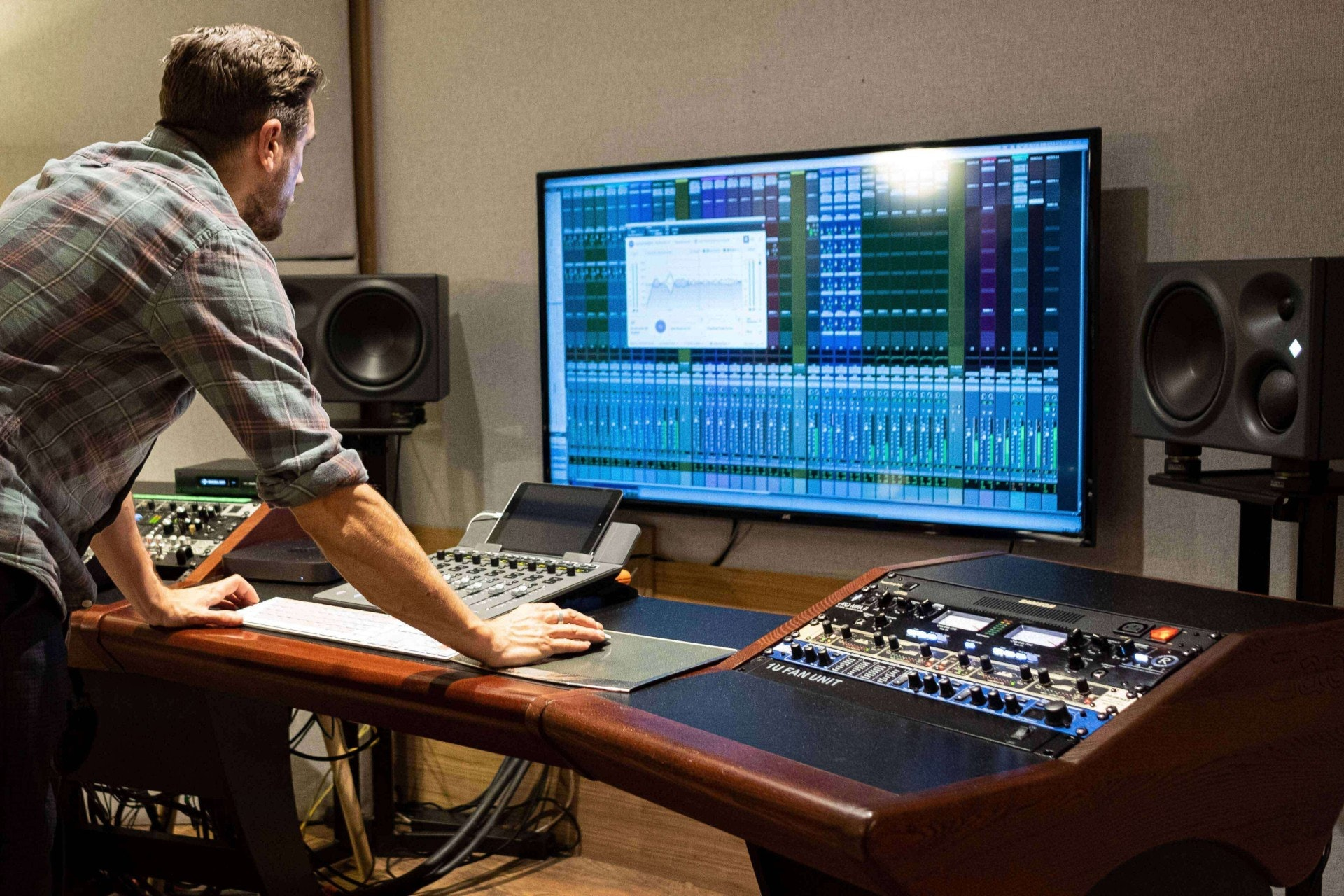 An inside shot of an LA recording studio  with active monitors, large display screen, and more