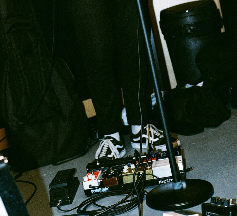 Close up shot of a guitarist and pedal board inside a Pirate Studios rehearsal studio
