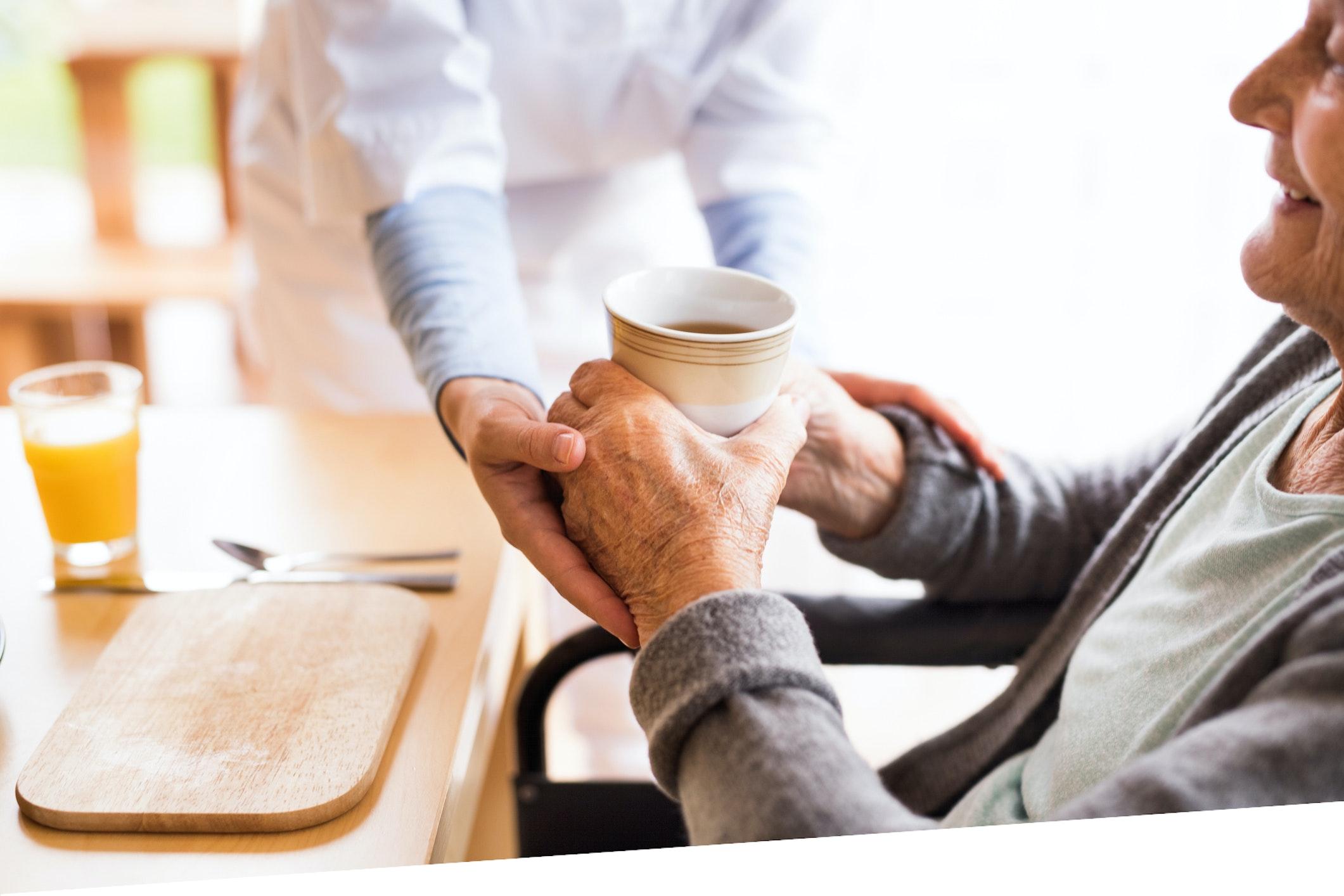 Altenpflegerin reicht betagter Dame einen Kaffeebecher