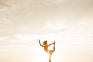 Woman in yoga pose with sun