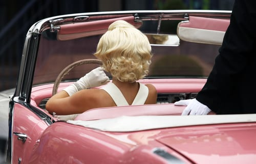 Model looking like Marilyn Monroe sitting behind the wheel of a pink convertible.