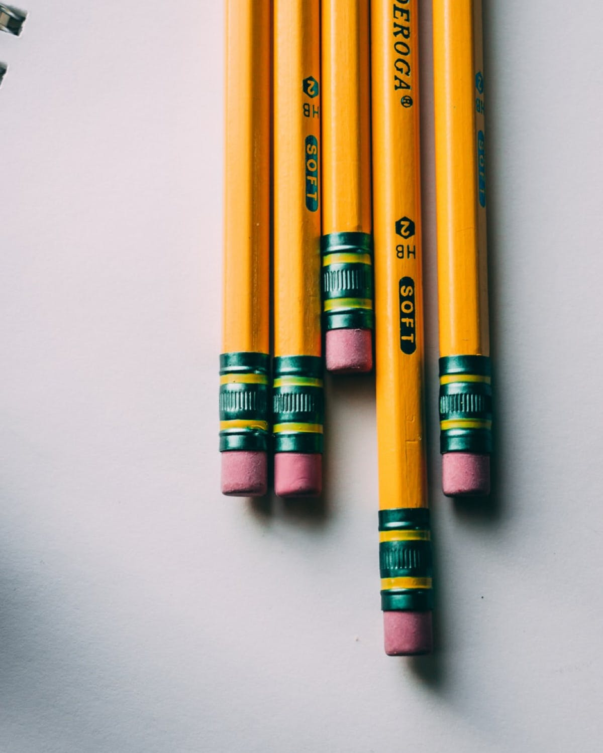 5 yellow pencils on white paper