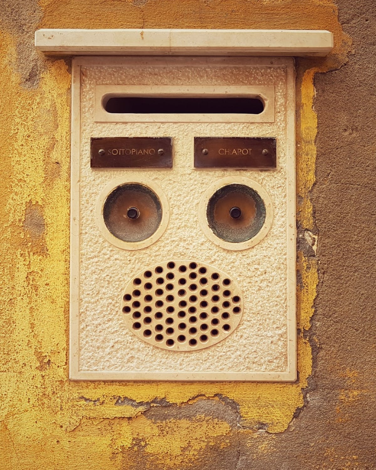 Cream intercom on brick wall