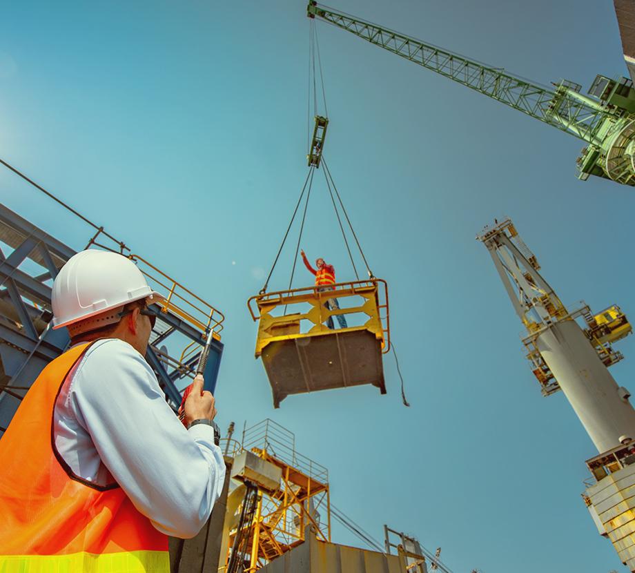Men on construction site using a crane