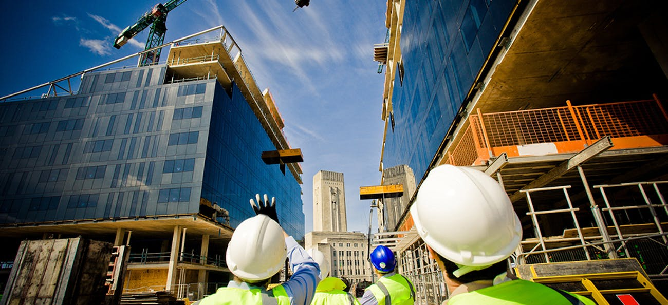 Construction workers looking up at a crane