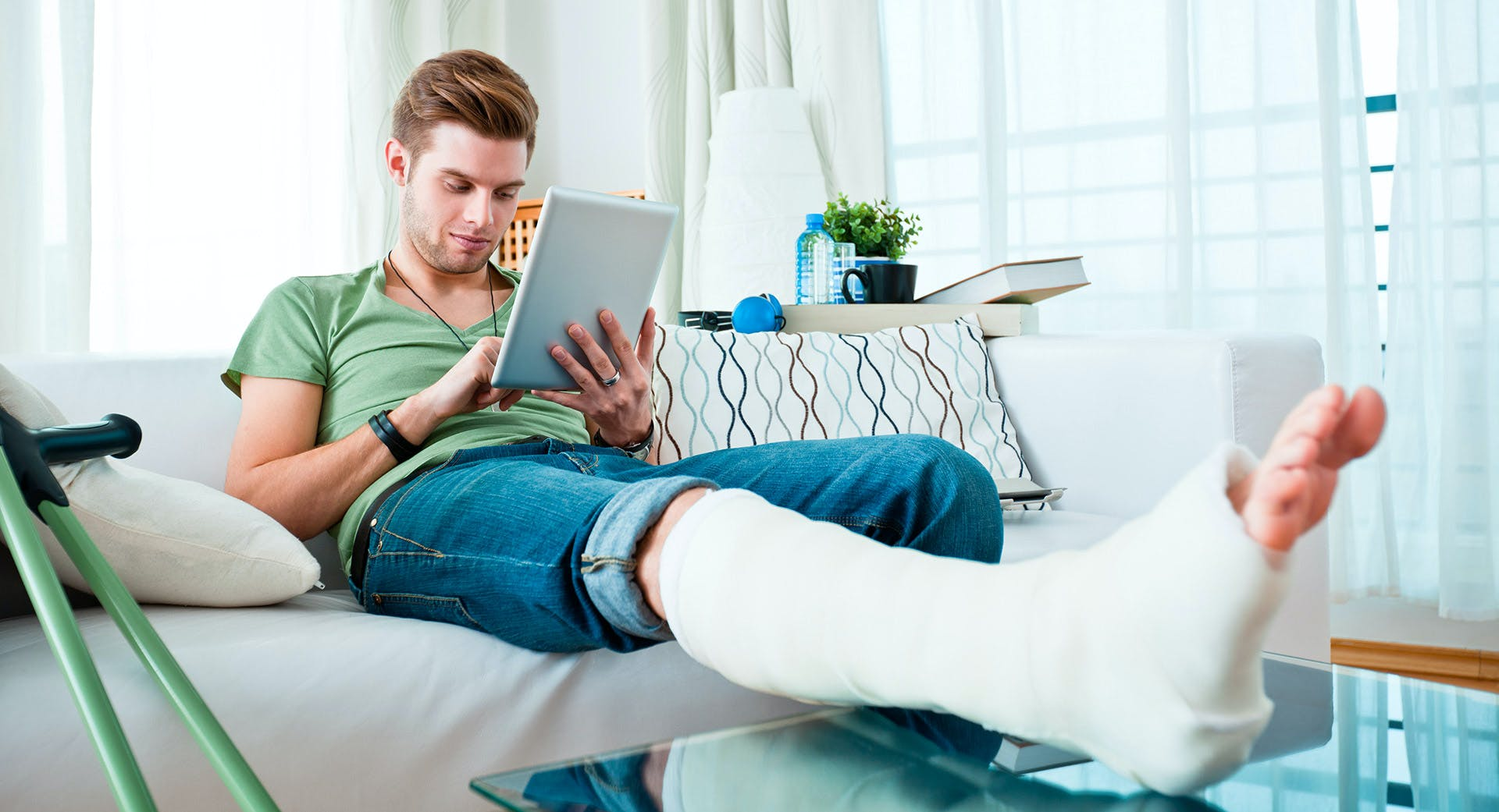 Injured man with lower leg cast resting on coffee table