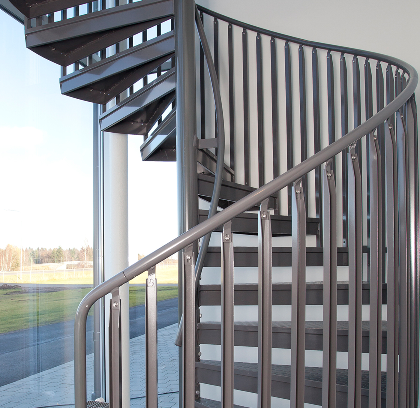 Powder coated spiral staircase with handrail on center tube and childsafe railing