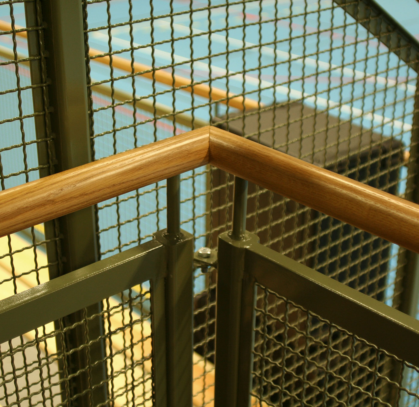 Detail picture with wooden handrail and railing in crenelated mesh