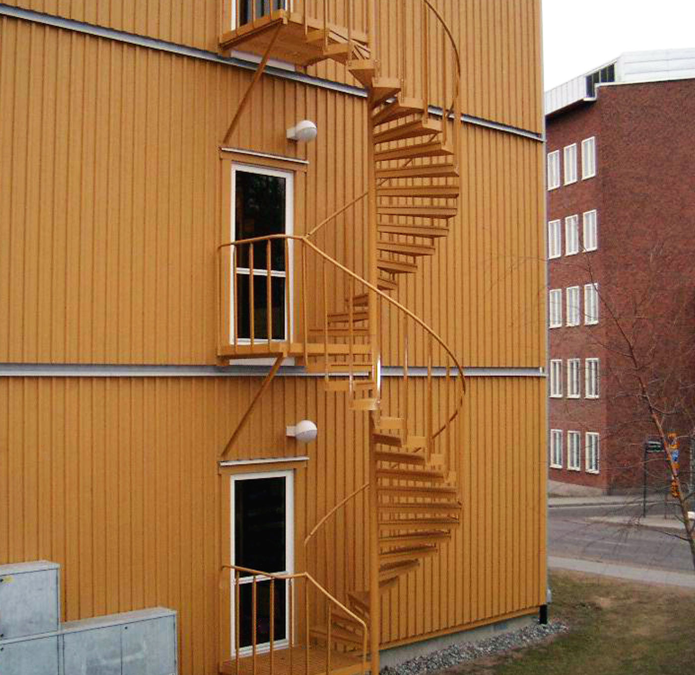 Powder coated spiral staircase outdoors with industrial railing