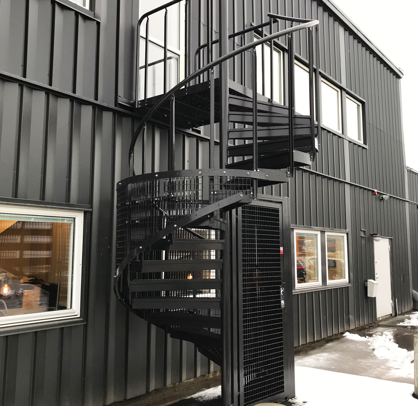 Powder coated outdoor spiral staircase with quarter protective cage
