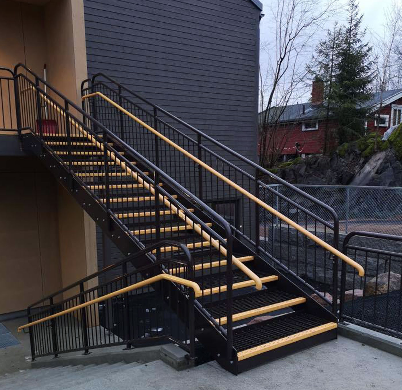 Powder coated straight staircase with grating steps and inner handrail in wood
