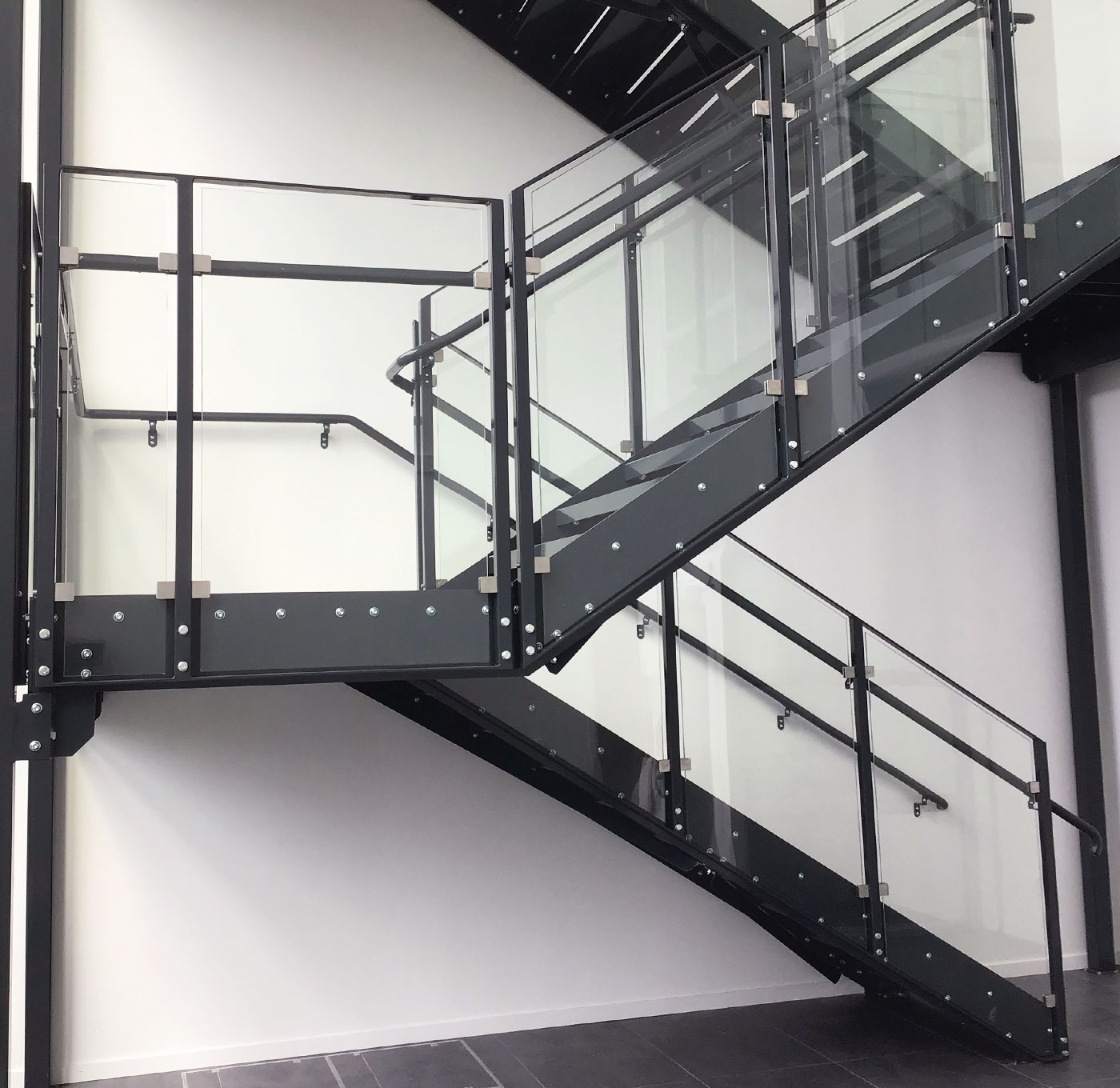 Straight staircase with powder coated inner handrail and glass railing