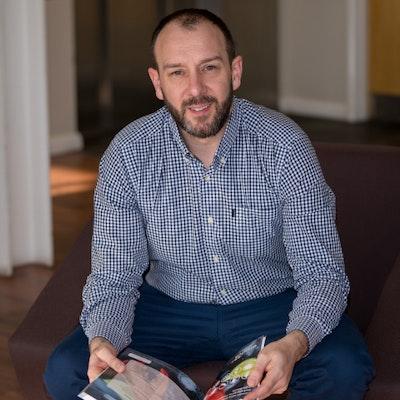 Erudus founder, Jon Shayler, sitting holding a magazine.
