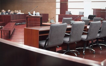 Courtroom with oak wooden tables flooring and grey office chairs with small audience
