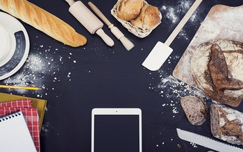 Phone on cooking worktop surrounded by baked goods and notebooks