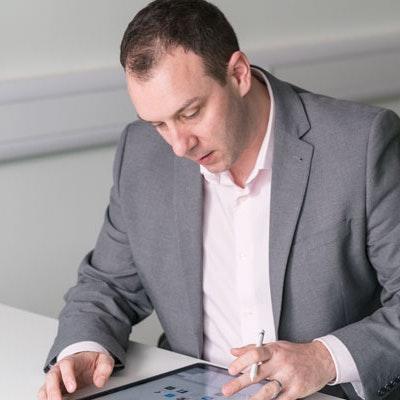 Jon Shayler of Erudus at desk looking at digital tablet