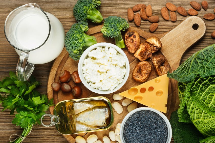 jug of milk on a table with various cheeses, mushrooms, nuts, fish, chia seeds and broccoli on a wooden chopping board
