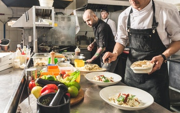 A group of chefs in a restaurant kitchen preparing dishes with lots of different ingredients