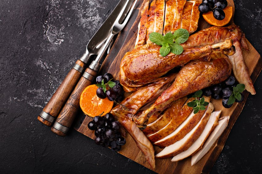 crispy cooked turkey sliced and garnished with grapes and orange on a wooden chopping board