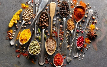 a colourful array of herbs and spices on various gold and silver brass spoons