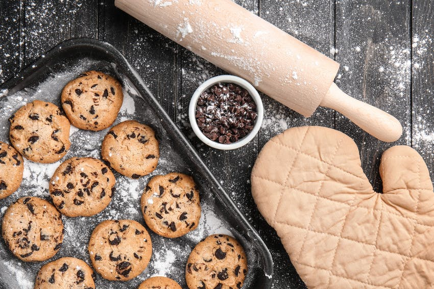 a tray of 12 chocolate chip cookies next to a small dish of chocolate chips, a rolling pin and an oven glove all dusted with flour