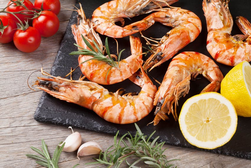 shrimp on a black display board with sliced lemon cherry tomatoes and garlic