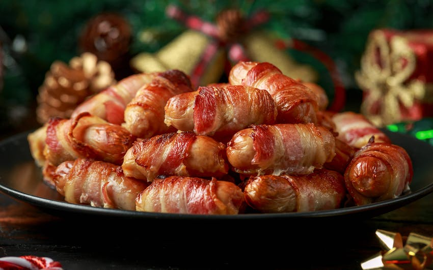 a black plate piled with cocktail sausages wrapped in bacon