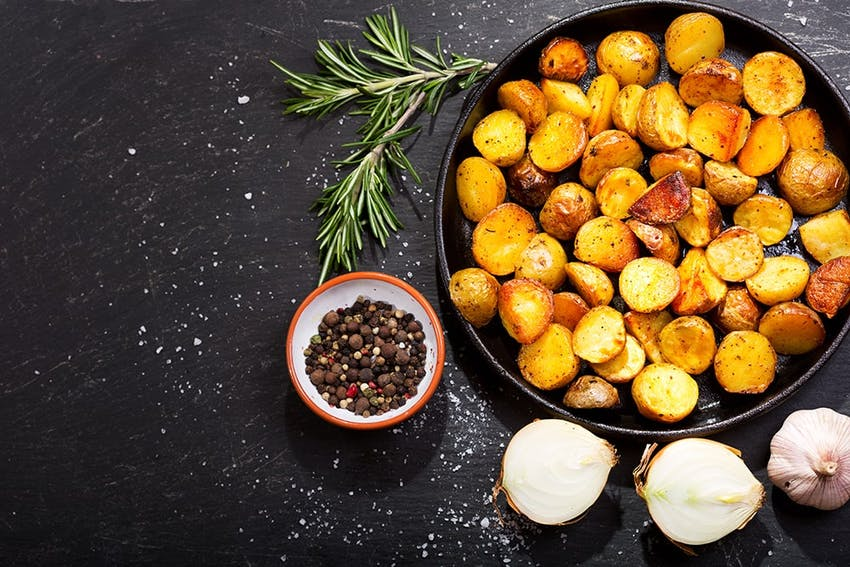 a bowl of crispy roast potatoes with a side dish of peppercorns, onions and a garlic bulb