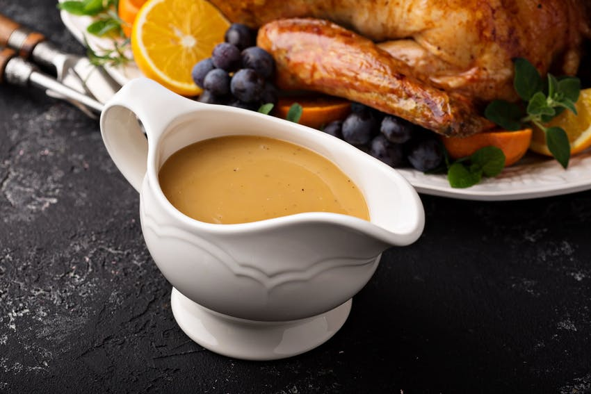 a white china gravy boat filled with gravy in front of a roasted turkey