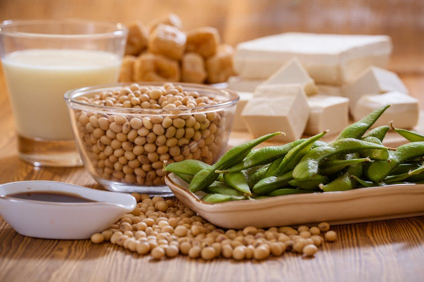 a large clear bowl of soya beans behind a tray of edamame beans, soy sauce and a glass of soya milk