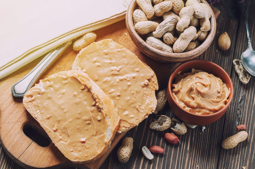 two slices of peanut butter toast on a wooden chopping board next to a dish of peanuts and a dish of crunchy peanut butter