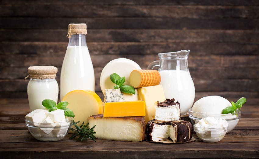 bottles of milk, cheese and cream on a wooden table
