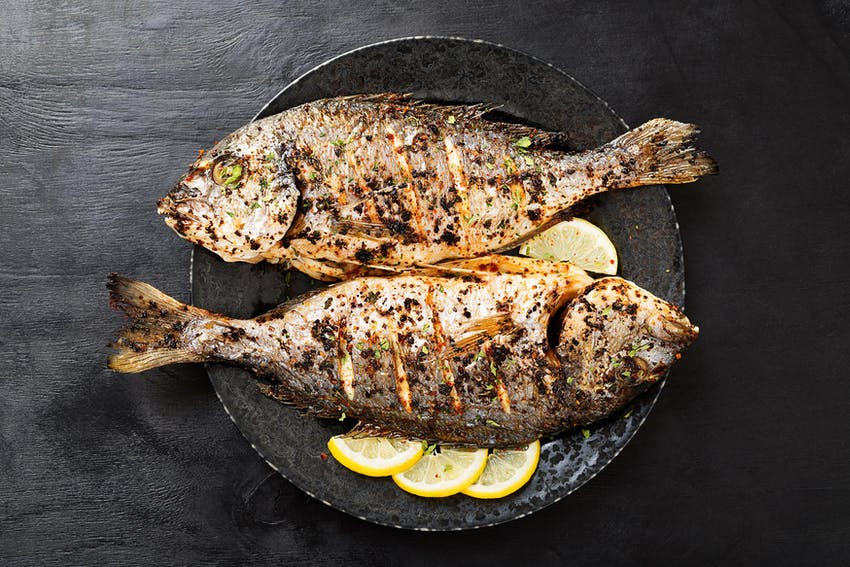two grilled fishes garnished in herbs and spices on a bed of sliced lemon in a black bowl