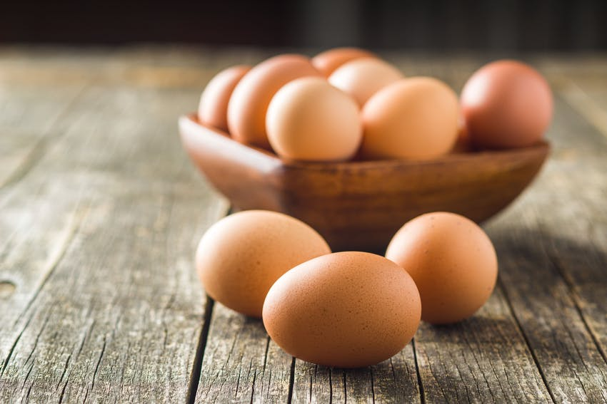 three eggs on a wooden table in front of a square wooden bowl filled with eggs