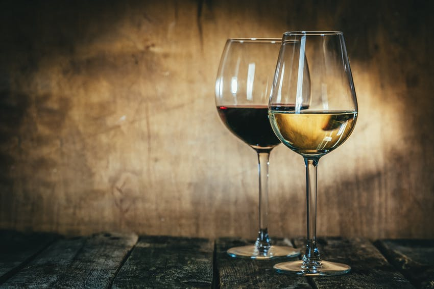 two glasses of wine, one white and one red on a rustic table near a wooden rustic wall