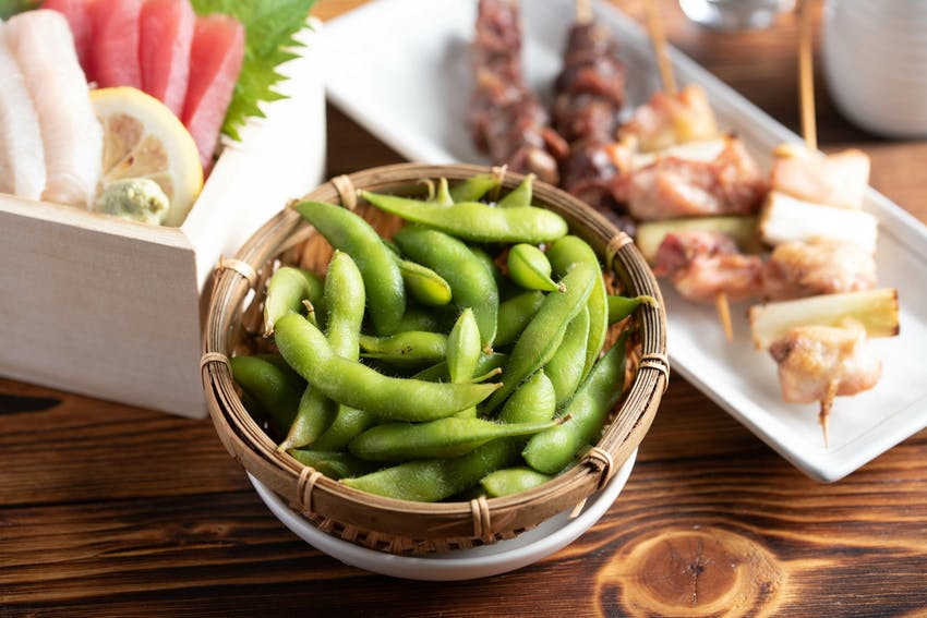 a small wooden bowl of edamame soya beans