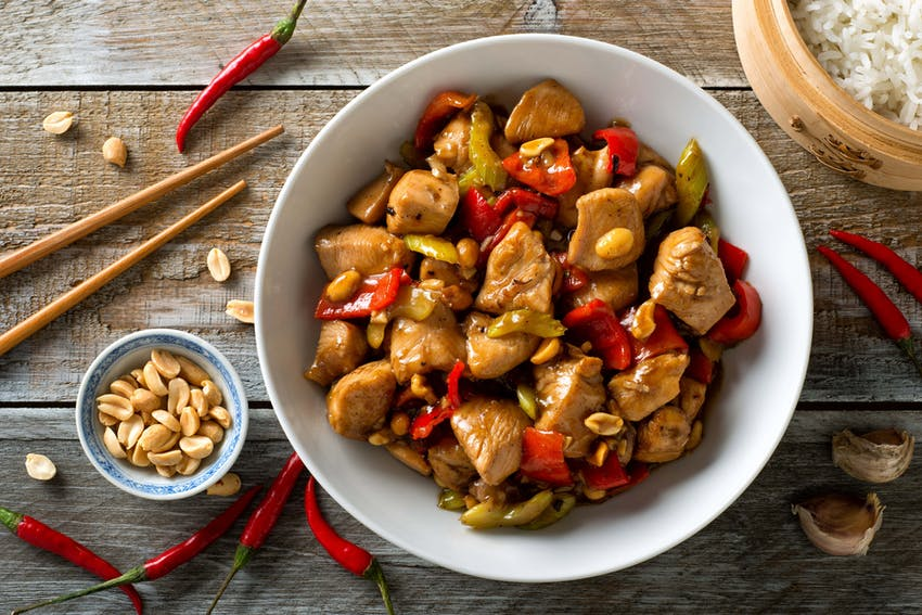 a bowl of satay chilli chicken topped with peanuts