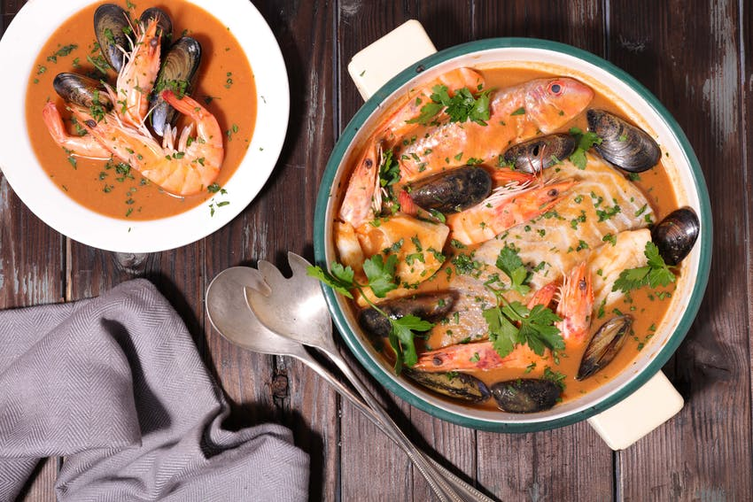a large hotpot of bouillabaisse next to a smaller serving dish of bouillabaisse topped with fresh herbs