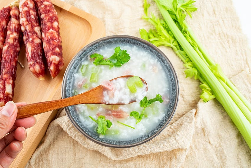 a grey ceramic bowl filled with soup topped with celery next to a wooden chopping board of chorizo and celery sticks