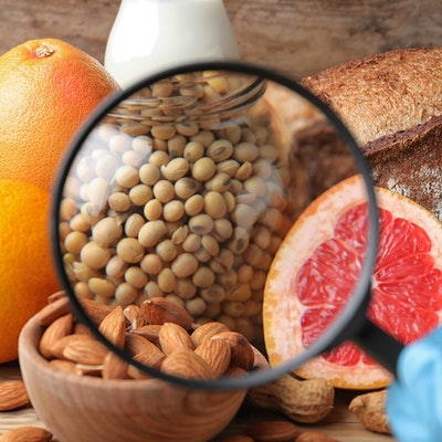 a magnifying glass focusing in on almonds, crustaceans, soyabeans, eggs and grapefruit