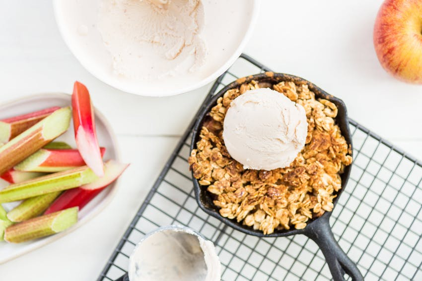 a small cast iron filled with a baked apple crumble topped with a scoop of creamy vanilla ice cream
