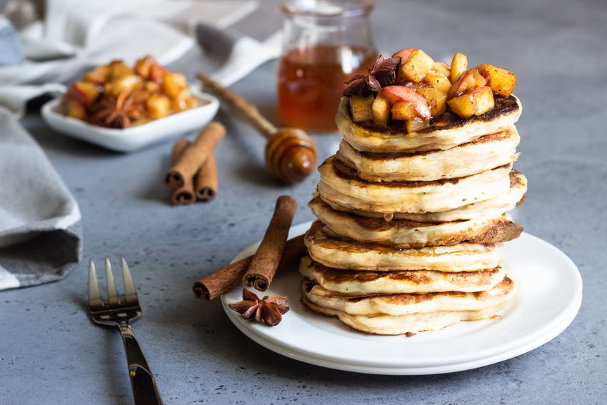 a white plate with a stack of eight pancakes with stewed apples on top and presented with two cinnamon sticks